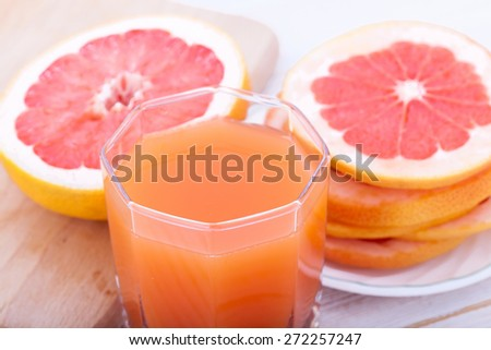 Glass of juice with fresh citrus grapefruit on white wooden table. Unusual top view - stock photo