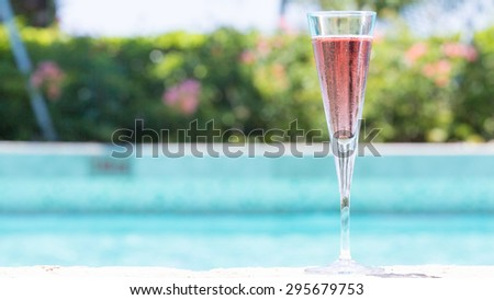 Glass of Kir Royal cocktail on the pool nosing at the tropical resort. Horizontal, wide screen, cocktail on right side - stock photo