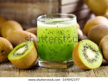 glass of kiwi juice with fresh fruits on wooden table - stock photo