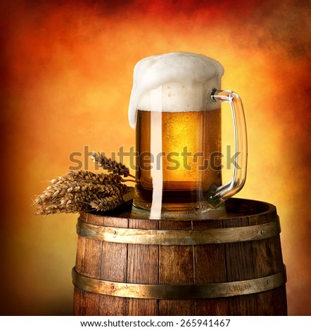 Glass of lager and wheat on a wooden barrel - stock photo