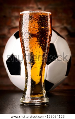 glass of lager with soccer ball on table against brick wall - stock photo