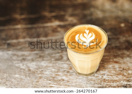 glass of latte coffee on wooden vintage table. - stock photo