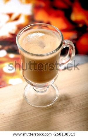 glass of latte macchiato coffe on wooden table and colorful background - stock photo