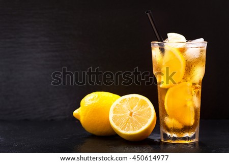 glass of lemon iced tea with fresh fruit on dark background - stock photo