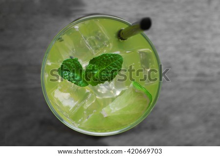 Glass of lemon soda with fresh mint on rustic wooden background - stock photo
