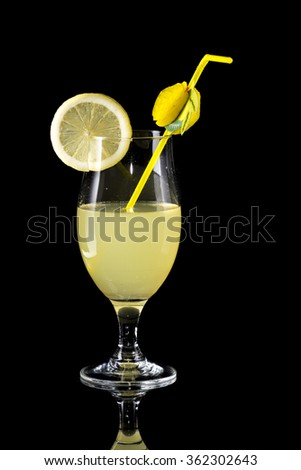 Glass of lemonade with bendie and lemon slice on black mirror background with reflection - stock photo