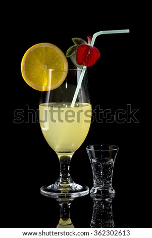 Glass of lemonade with bendie and orange slice and small glass on black mirror background with reflection - stock photo