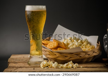 Glass of light beer on black background - stock photo