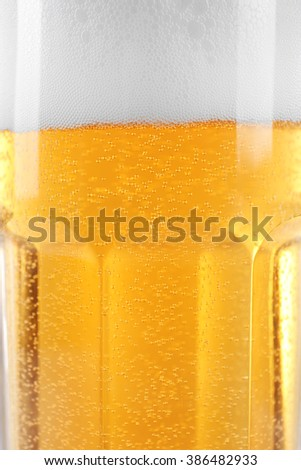 Glass of light beer with bubbles and froth, close up - stock photo