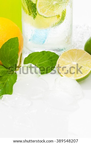 Glass of lime-flavored mineral water, decorated with ice cubes, lime slices and mint leaves; Refreshing summer drink - low in calories - stock photo