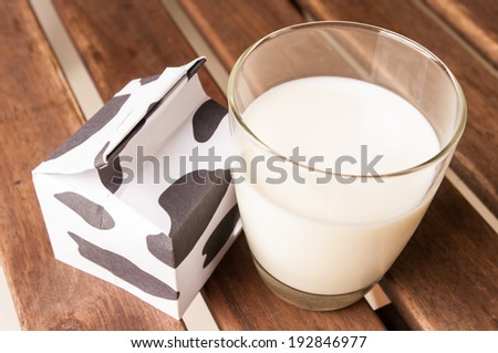 glass of milk, a carton of milk on wooden table. - stock photo