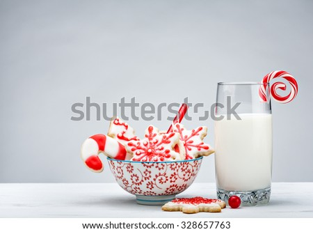 Glass of Milk, and bowl of red and white sugar cookies for Santa over a white background. - stock photo