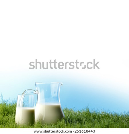 Glass of milk and jar on fresh grass meadow  - stock photo
