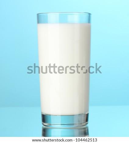Glass of milk on blue - stock photo