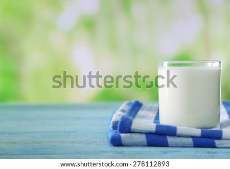 Glass of milk on wooden table, on green nature background - stock photo