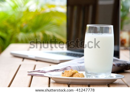Glass of milk with cookies and early morning newspaper and computer in background. - stock photo