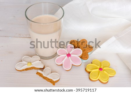 Glass of milk with cookies. Flower shaped colorful cookies on white wooden background - stock photo