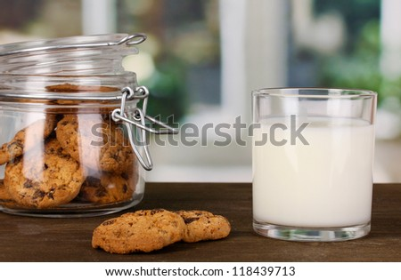 Glass of milk with cookies on wooden table on windows background close-up - stock photo