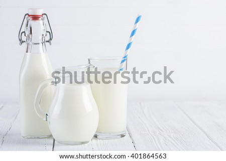 Glass of milk with stripped blue paper straw and jug of milk and milk bottle on white wooden table - stock photo