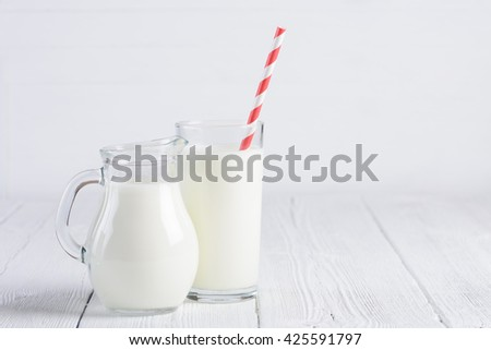 Glass of milk with stripped red paper straw and jug of milk on white wooden table - stock photo