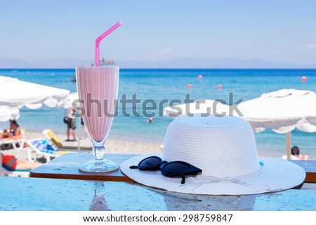 Glass of milkshake, hat and sunglasses on a table with a view of a beach. Rhodes, Greece - stock photo