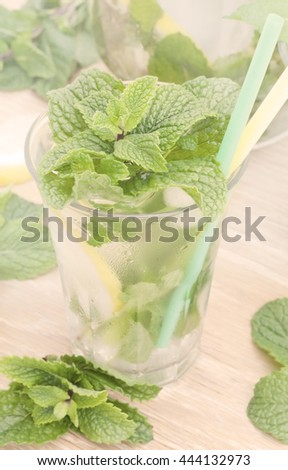 Glass of mint lemonade. Fresh drink with lemon juice and spearmint. Toned image - stock photo