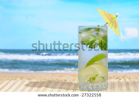 Glass of Mojito cocktail with umbrella at the beach - stock photo