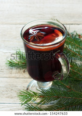 Glass of mulled wine and fir over wood background - stock photo