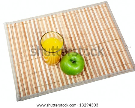 Glass of orange juice and green apple on napkin - stock photo