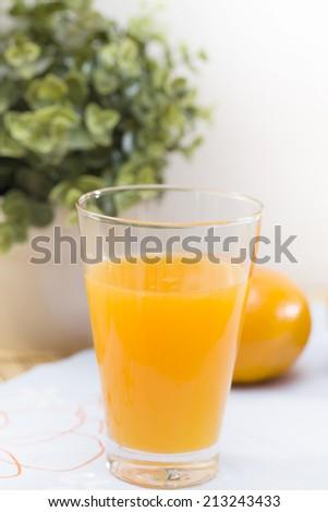 Glass of orange juice and orange - stock photo