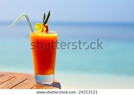 Glass of orange  juice on a beach table - stock photo
