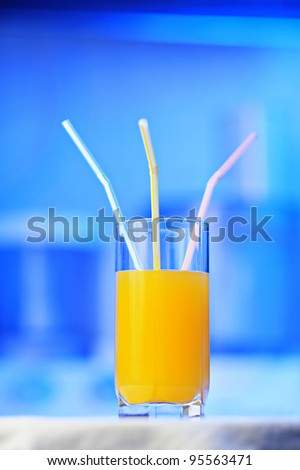 Glass of orange juice with three straws, shallow DOF focus on a middle straw - stock photo
