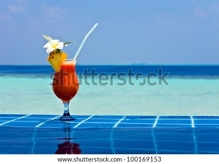 Glass of papaw juice is on edge of pool made from glazed tile  in tropical hotel, Maldives - stock photo