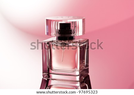 glass of perfume over abstract pink background - stock photo