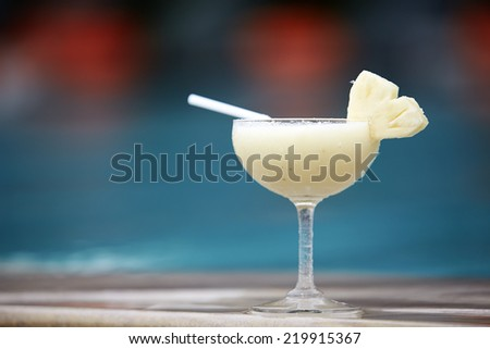Glass of pinacolada cocktail standing on the swimming pool - stock photo
