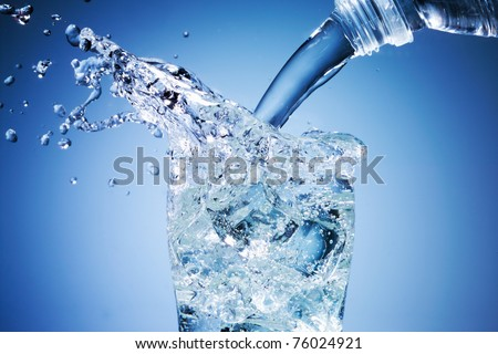 Glass of pouring water with ice - stock photo