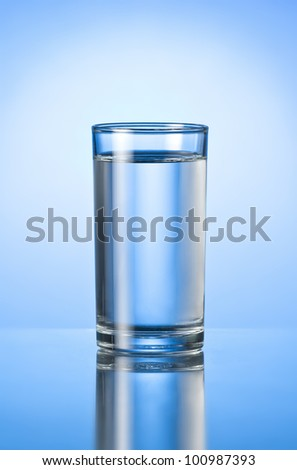 glass of pure water on blue glossy background - stock photo