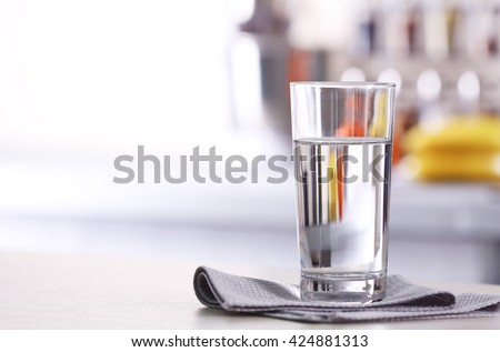 Glass of pure water on kitchen table - stock photo