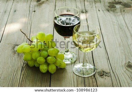 glass of red and white wine and cluster of grapes on wood table - stock photo