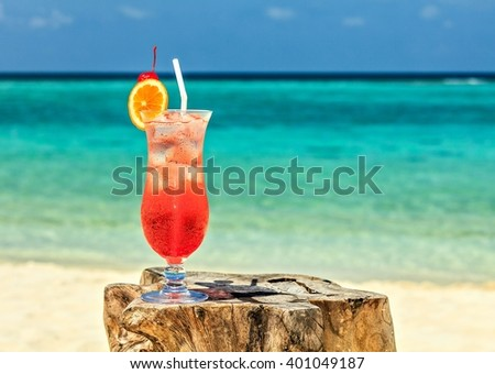 Glass of red drink is on the beach table, Maldives, The Indian Ocean - stock photo