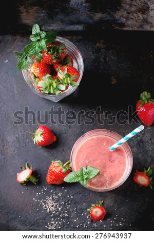 Glass of red strawberry smoothie with chia seeds, served with retro cocktail tube, fresh mint and strawberries over dark background. - stock photo