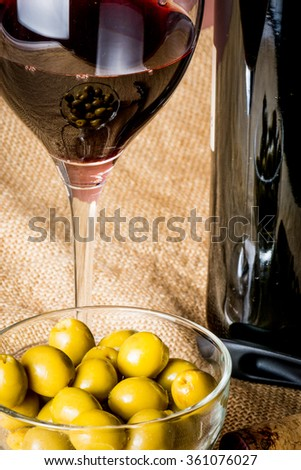 glass of red wine, a bottle of red wine and a bowl of olives - stock photo