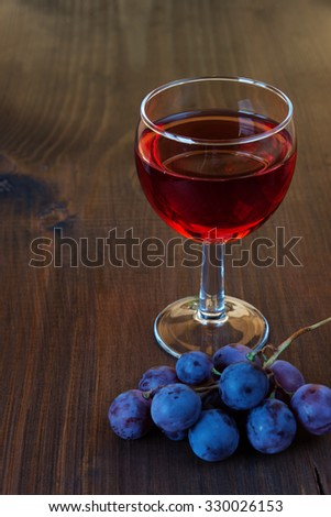 Glass of red wine and a cluster of grapes on dark wooden board - stock photo