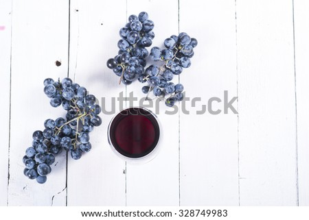 glass of red wine and blue grapes on white wooden table background - stock photo