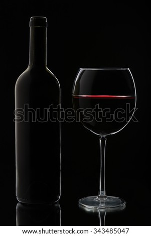 Glass of red wine and bottle. Isolated on black background - stock photo