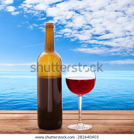 Glass of red wine and bottle on wooden background. Summer blurred background. Tropical landscape, sea. Flat mock up for design. - stock photo