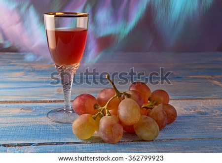 Glass of red wine and bunch of pink grapes on wooden table and waving in wind curtain.   - stock photo