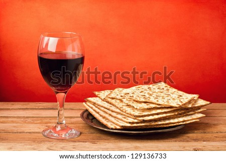 Glass of red wine and matzo on wooden table over grunge red background - stock photo