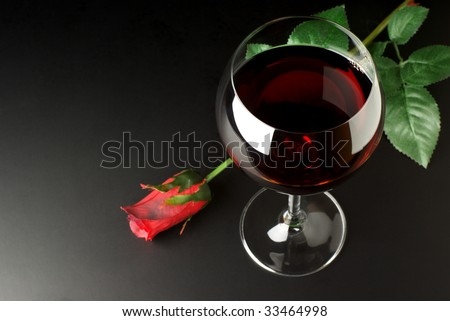 Glass of red wine and red rose on black background. - stock photo