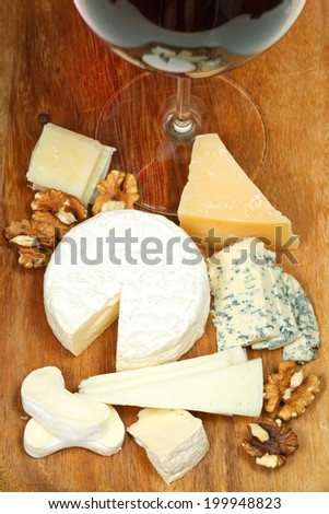 glass of red wine and various cheeses on wooden plate close up - stock photo